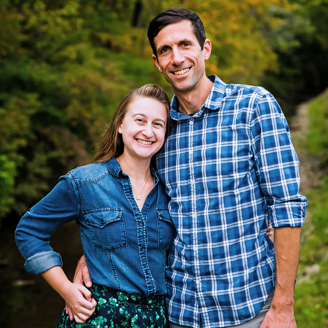 Julia Spangler and Mark Clayton smiling and standing in a green wooded setting